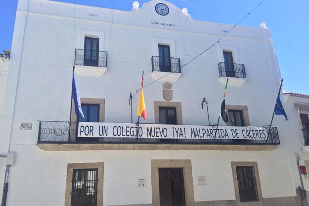Pancarta por un nuevo colegio en Malpartida en la fachada del Ayuntamiento de Malpartida de Cáceres